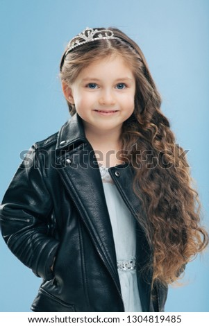 Vertical shot of attractive small female child has long curly hair, wears crown and leather jacket s Stock photo © vkstudio
