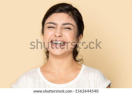 Cheerful good looking woman has toothy smile, enjoys nice track in earphones, updates playlist on sm Stock photo © vkstudio