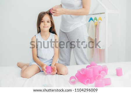Cropped shot of unrecognizable mother winds curlers to her pretty daughter, going to make nice hairs Stock photo © vkstudio