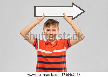 boy holding big white rightwards thick arrow Stock photo © dolgachov