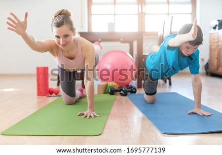 Stock photo: Mother and son in coronavirus quarantine having workout at home
