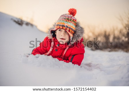Boy in red fashion clothes playing outdoors. Active leisure with children in winter on cold days. Bo Stock photo © galitskaya