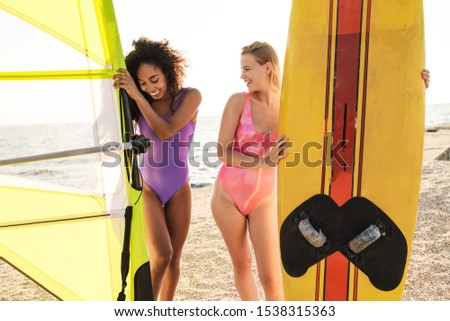 Image of seductive multinational women smiling and holding placards Stock photo © deandrobot