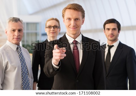 young business man points at camera while smiling behind laptop Stock photo © feedough