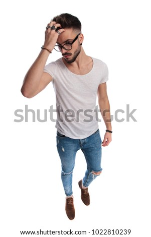 young casual man wearing glasses passes his hand through  hair  Stock photo © feedough