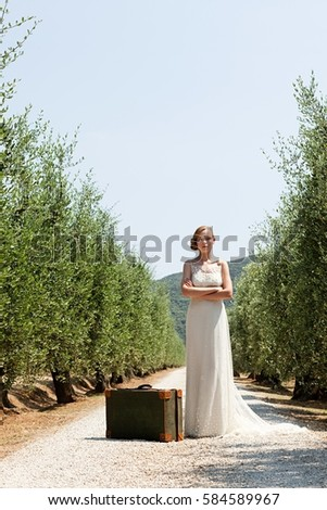 Bride with suitcase on country road, arms crossed Stock photo © IS2