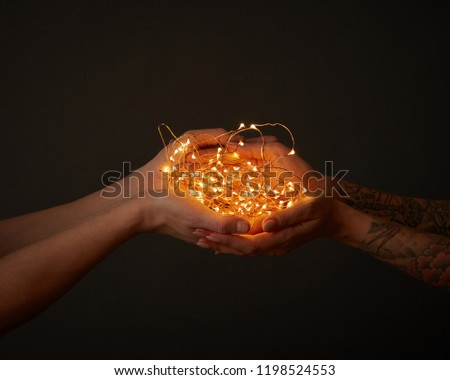 a bunch of christmas garlands holds a male and female hand with a tattoo on a black background with stock photo © artjazz
