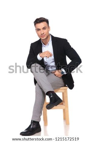 attractive businessman sitting on wooden chair with legs crossed Stock photo © feedough