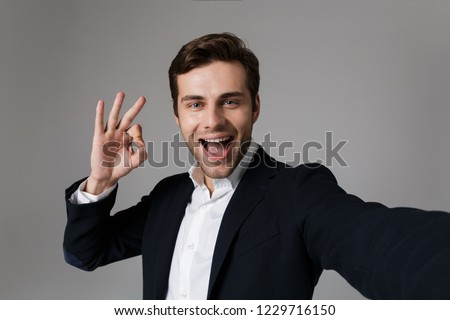 image of joyous businessman 30s in formal suit showing ok sign o stock photo © deandrobot