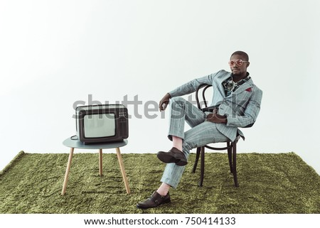 fashion man wearing sunglasses sits cross-legged on wooden chair Stock photo © feedough
