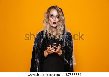 Young wizard woman 20s wearing black costume and halloween makeu Stock photo © deandrobot