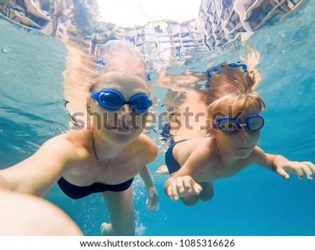 Anya fiú búvárkodik szemüveg úszás medence Stock fotó © galitskaya