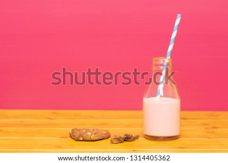 straw and half bottle of strawberry milkshake with cookie crumbs stock photo © sarahdoow