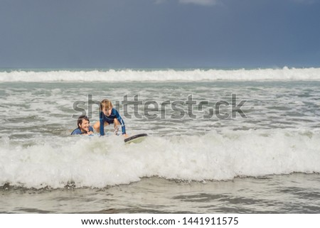 Father teaching his young son how to surf in the sea on vacation or holiday. Travel and sports with  Stock photo © galitskaya