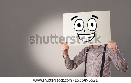 Student holding a paper with laughing emoticon in front of his f Stock photo © ra2studio
