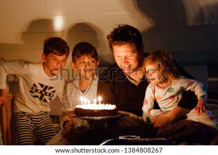 Happy little kid boy celebrating his birthday and blowing candles on homemade baked cake, indoor. Bi Stock photo © galitskaya