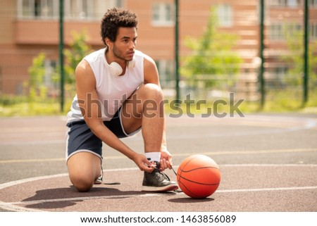 Young professional basketball player tying shoelace of sneaker Stock photo © pressmaster