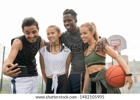 Young affectionate sporty friends in activewear looking at smartphone camera Stock photo © pressmaster