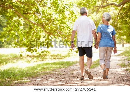 back view of active senior couple walking hand in hand at the beach with mountains in the background stock photo © wavebreak_media