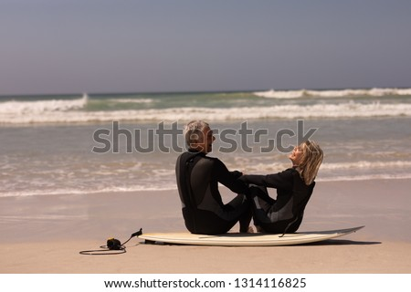 Side view of happy senior couple sitting on surfboard at beach in the sunshine 4k Stock photo © wavebreak_media