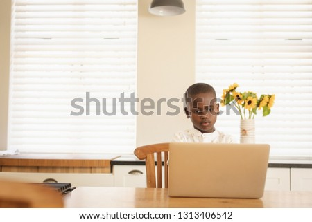 Front view of African American boy using laptop at dining table in kitchen at home Stock photo © wavebreak_media