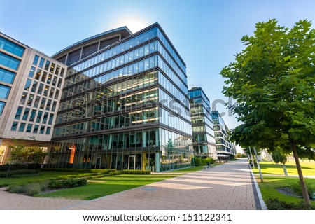 glass office building and view of the modern city with passing cars and railway 4k video 240fps 2 stock photo © artjazz