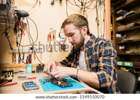Professional repairman bending over broken smartphone and fixing tiny details Stock photo © pressmaster