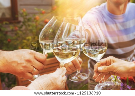 Hands of a group of people cheering with white wine and rising g Stock photo © dashapetrenko