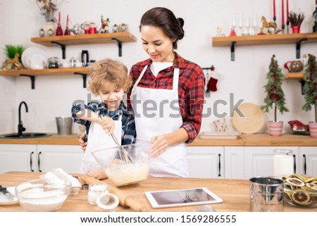 Little boy learning to whisk eggs for dough while standing close to his mother Stock photo © pressmaster