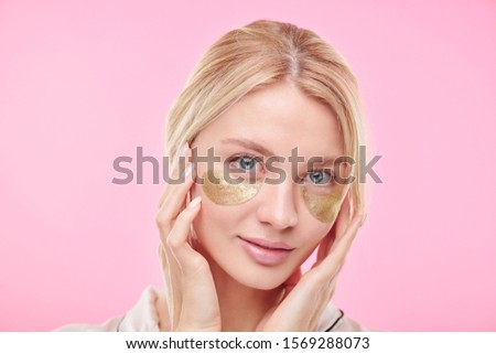 Young beautiful blond woman with golden revitalising under-eye patches Stock photo © pressmaster