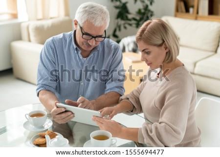 Jubilado hombre jóvenes hija senalando touchpad Foto stock © pressmaster
