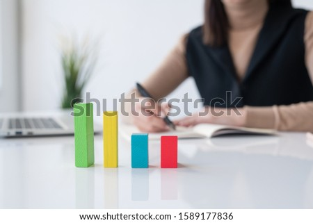 Multi-color cube chart on desk on background of female banker making notes Stock photo © pressmaster