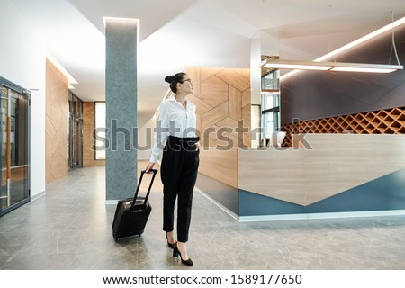 Businesswoman moving along hotel lounge with reception counter on background Stock photo © pressmaster