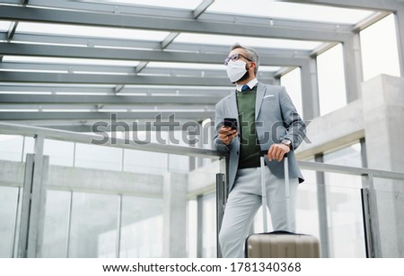 Young business travelers with baggage standing by one of elevator doors in hotel Stock photo © pressmaster