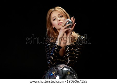 Pretty girl in black glittering dress holding disco ball while relaxing on couch Stock photo © pressmaster