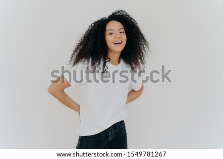 Portrait of cheerful millennial woman keeps hands behind back, dressed in casual wear, laughs from s Stock photo © vkstudio