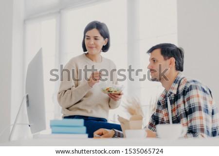 Vrouwelijke mannelijke collega's samenwerken samen eten Stockfoto © vkstudio