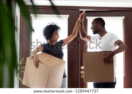 Happy young couple enter own modern house, buy real estate, carry cardboard boxes with indoor plant  Stock photo © vkstudio