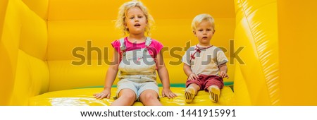 A boy and a girl ride from an inflatable slide BANNER, LONG FORMAT Stock photo © galitskaya