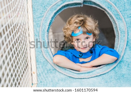 Blonde curly little boy in blue costume of superman in round window Stock photo © pressmaster