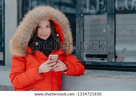 Pleasant looking young female in red jacket, holds modern smart phone, checks bank account, waits fo Stock photo © vkstudio