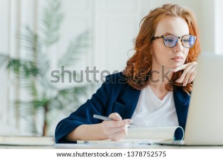 Sério experiente feminino treinador registros bloco de notas Foto stock © vkstudio