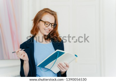 Happy ginger young female plans working schedule, writes in notebook, makes notes of useful informat Stock photo © vkstudio