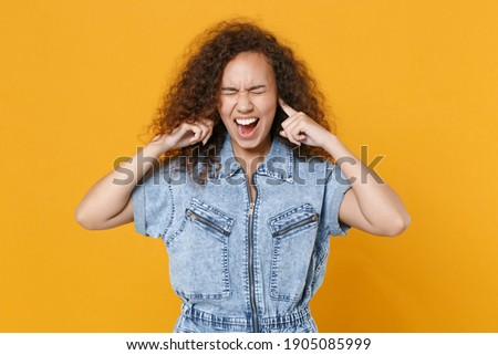 Young woman with curly Afro hair covers ears, shouts as demands be quiet, cant stand noise, keeps mo Stock photo © vkstudio