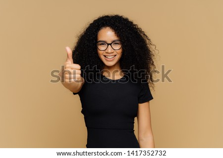 Waist up shot of satisfied supportive woman shows thumb up, cheers best friend, encourages for excel Stock photo © vkstudio