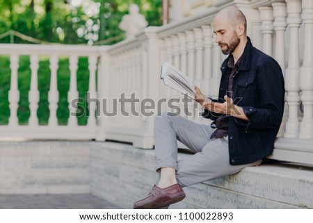 Attractive bald man reads attentively interesting book, gestures with hand, has stunning plot, tries Stock photo © vkstudio