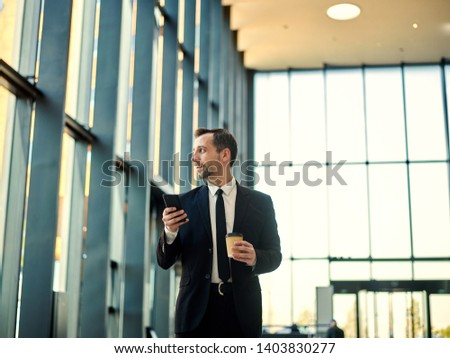 Thoughtful middle aged male with stubble holds smart phone near mouth, being deep in thoughts, think Stock photo © vkstudio