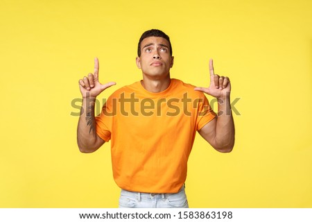 Young sad man with tattooed arm in orange t-shirt, white pants, looking up lonely with sadness and r Stock photo © benzoix