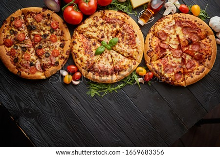 Freshly served, three various pizzas placed among tasty ingredients. Top view Stock photo © dash
