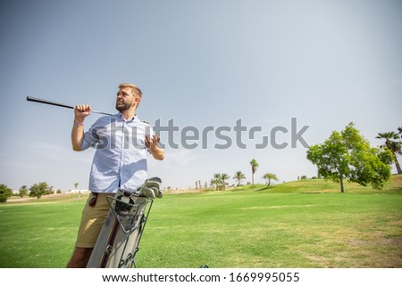A man on a golf course examines the equipment and prepares for a sporting event at the golf club Stock photo © ElenaBatkova